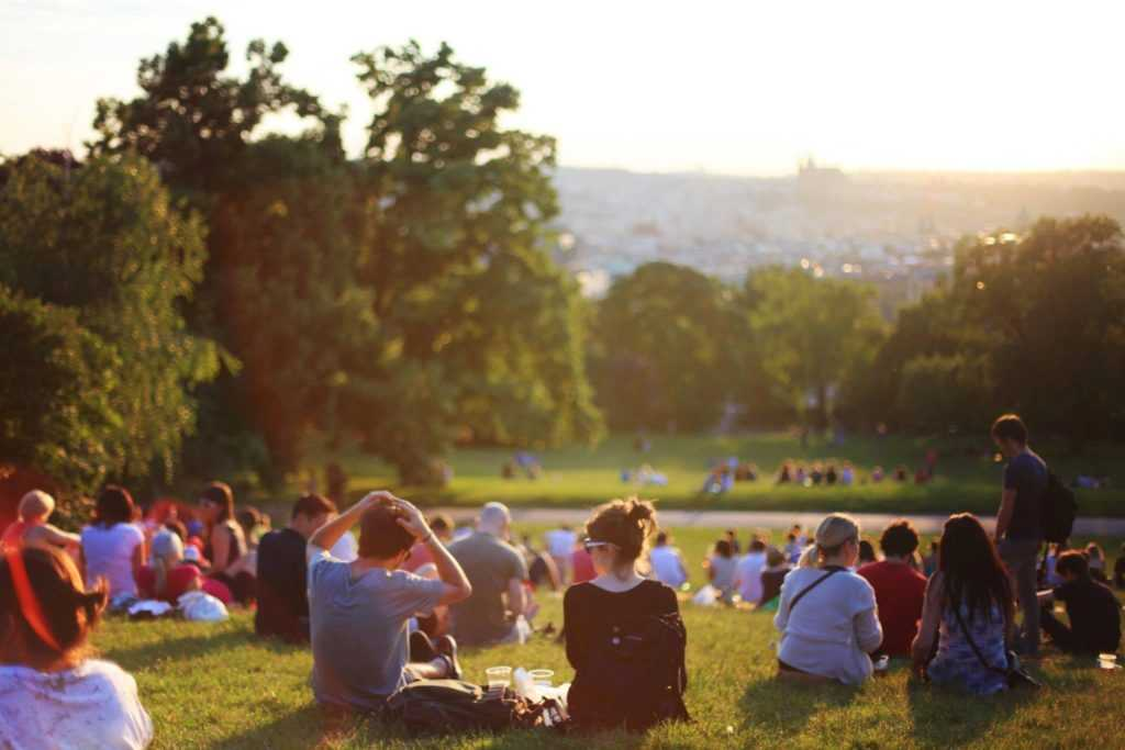 People overlooking the city while sitting on lawn.