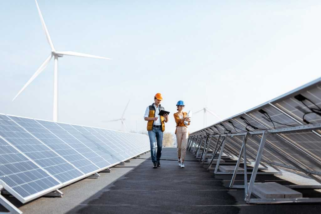 View on the rooftop solar power plant with two engineers walking and examining photovoltaic panels.